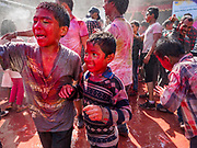 "12 MARCH 2017 - BHAKTAPUR, NEPAL: Boys at the Holi celebration in ""Pottery Square"" in Bhaktapur by throwing colorful powder on each other and dousing each other with water. Holi, a Hindu religious festival, has become popular with non-Hindus in many parts of South Asia, as well as people of other communities outside Asia. The festival signifies the victory of good over evil, the arrival of spring, end of winter, and for many a festive day to meet others. Holi celebrations in Nepal are not as wild as they are in India.     PHOTO BY JACK KURTZ"