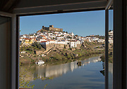 Historic hilltop walled medieval village of Mértola with castle, on the banks of the river Rio Guadiana, Baixo Alentejo, Portugal, Southern Europe framed by hotel window