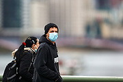 People wearing face protective masks walk in central London on Saturday, Mar 13, 2021. Coronavirus has hit the UK hard, with the country recording more than 3m cases and 125,000 deaths linked to the disease. (VXP Photo/ Vudi Xhymshiti)