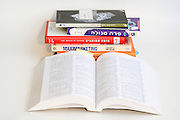 Cutout of a pile of Hebrew books on white background
