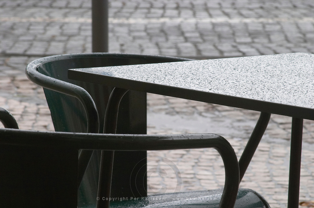 Chairs and table outside at a restaurant terrace in rain. Street view. Alfama district. Lisbon, Portugal