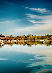 Tall blue skies with wispy clouds above the reflecting tree line at Klondike Park lake in Saint Charles, Missouri.