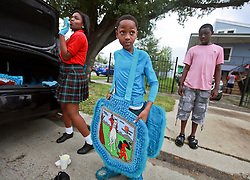 29 August 2014. Lower 9th Ward, New Orleans, Louisiana. <br /> Survivors of the storm. Mardi Gras Indian Michael 'Spy Boy' Tenner (10 yrs) of the Comanche Hunters prepares to lead a touching second line parade along Tennessee Street in the Lower 9th Ward in memory of those who perished in the storm 9 years ago. <br /> Photo; Charlie Varley/varleypix.com