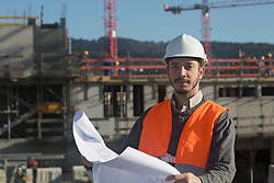 Portrait of a young male engineer holding blueprint at construction site, Freiburg Im Breisgau, Baden-Wuerttemberg, Germany