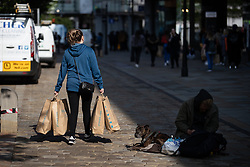 © Licensed to London News Pictures. 15/06/2020. Manchester, UK. A woman carries bags of shopping from Primark on Market Street . High street shops reopen in Manchester City Centre for the first time since measures forced non-essential retailers to close , in order to limit the spread of the Coronavirus . Photo credit: Joel Goodman/LNP