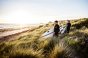 Surfers walking through the sand dunes at St Ouen's Bay, Jersey, holding their surfboards ready to get into the water.