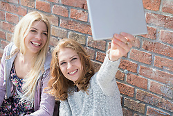 Two friends taking selfie with her digital tablet, Munich, Bavaria, Germany