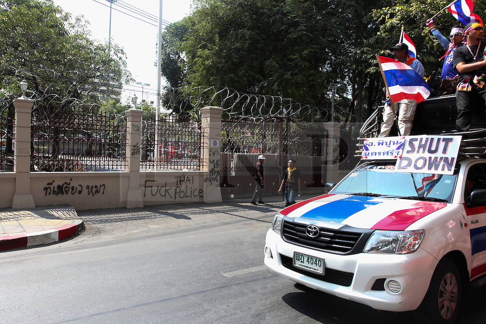 © Licensed to London News Pictures. 18/01/2014. A car with Anti-Government supporters drives past the anti-police graffiti covered walls at the Royal Thai Police Head quarters in response to an explosive device reportedly injuring as many as 30 people and killing one yesterday during an anti-government street rally in Bangkok, Thailand. Anti-government protesters launch 'Bangkok Shutdown', blocking major intersections in the heart of the capital, as part of their bid to oust the government of Prime Minister Yingluck Shinawatra ahead of elections scheduled to take place on February 2. Photo credit : Asanka Brendon Ratnayake/LNP