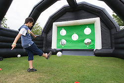 Boy playing a football scoring game at a Parklife summer activities event,