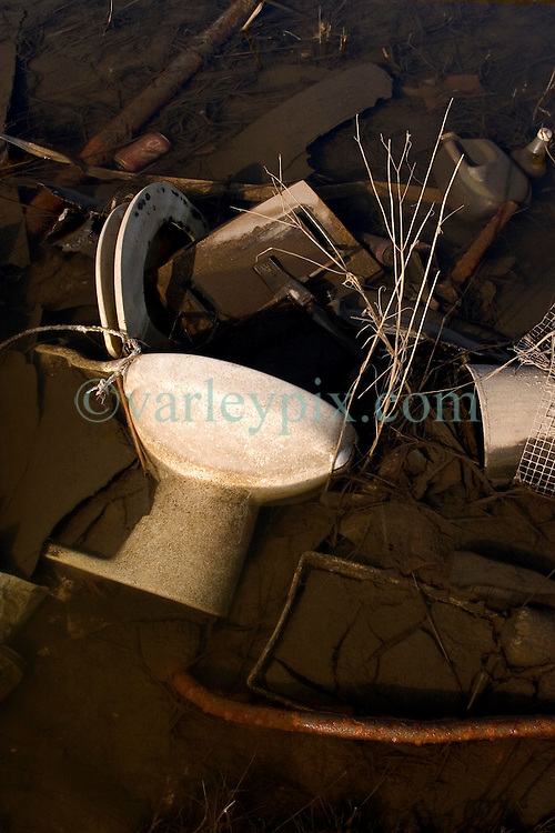30 Sept, 2005.  New Orleans, Louisiana. Lower 9th ward. Hurricane Katrina aftermath. <br /> The remnants of the lives of ordinary folks, now covered in mud as the flood waters remain. A toilet lies in the filthy flood waters. <br /> Photo; ©Charlie Varley/varleypix.com