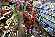 A traditionaly dressed Himba woman shops for staples and soda pop with her child in a supermarket in Opuwo, northwestern Namibia after receiving money from a tourist in exchange for a photograph. (From the book What I Eat: Around the World in 80 Diets.)