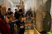 Visitors admire the ancient Egyptian Rosetta Stone in Room 4 of the British Museum, on 11th April 2018, in London, England.