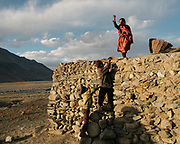 """Getting Kurut, dried curd, of the roof of a home. Life in Baiqara, a Wakhi High pasture inhabited for about 6 months of the year, from May until October. Guiding and photographing Paul Salopek while trekking with 2 donkeys across the """"Roof of the World"""", through the Afghan Pamir and Hindukush mountains, into Pakistan and the Karakoram mountains of the Greater Western Himalaya."""