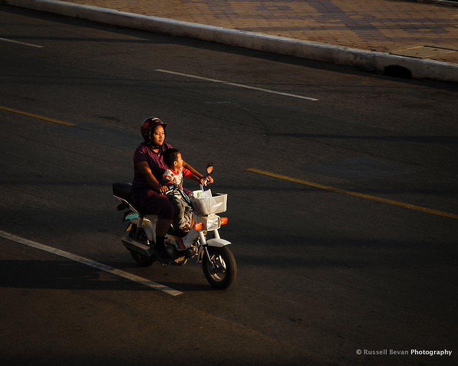 A mother rides with her small son on a moped in Phnom Penh, Cambodia