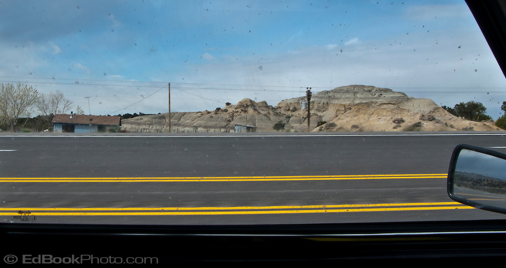 a rural home and rock formation along US 550 in northwest New Mexico seen through the window of a classic Mini Cooper with parallel yellow lines on the pavement.
