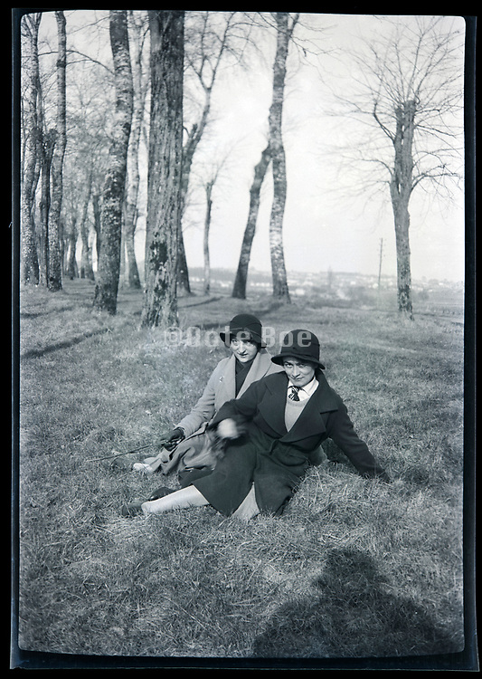 women sitting in a rural landscape with a trees lined path France circa 1920s