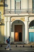 Man with backpack walking down street, Cuba, Havana