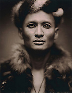 Fashion portrait of a mature man with luminous eyes who wears an ethnic costume made of fur.