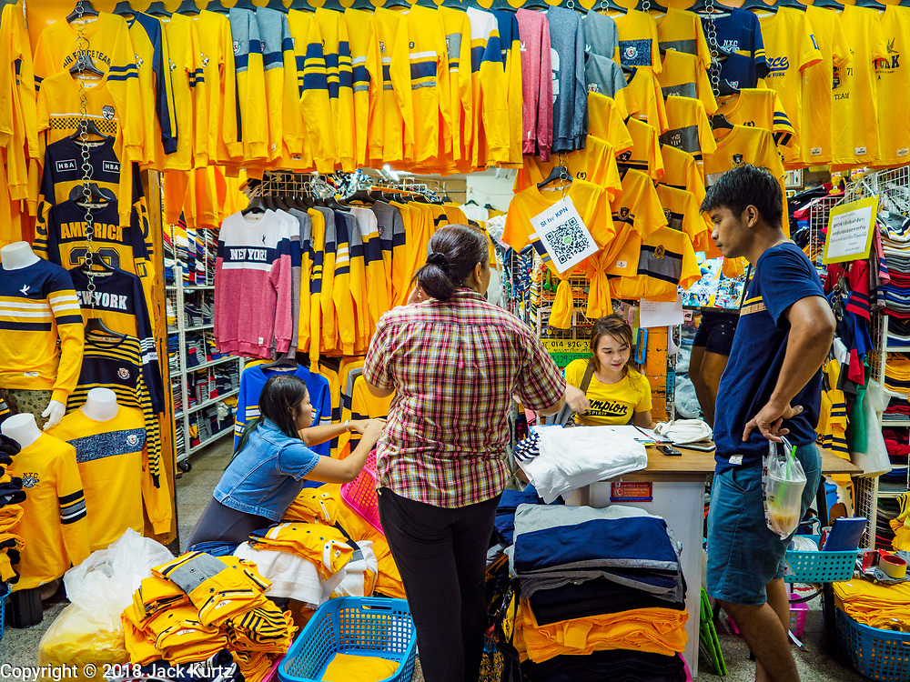 """03 JULY 2018 - BANGKOK, THAILAND: A vender in Bobae Market in Bangkok sells yellow shirts that save """"Long Live the King."""" The birthday of King Maha Vajiralongkorn Bodindradebayavarangkun, Rama X, is 28 July. The King, the only son of Thailand's late King Bhumibol Adulyadej, became the King of Thailand in 2016 after the death of his father. King Vajiralongkorn was born on 28 July 1952, a Monday. In Thai culture each day of the week has a color, and yellow is the color is associated with Monday, so people wear yellow for the month before his birthday to honor His Majesty.    PHOTO BY JACK KURTZ"""