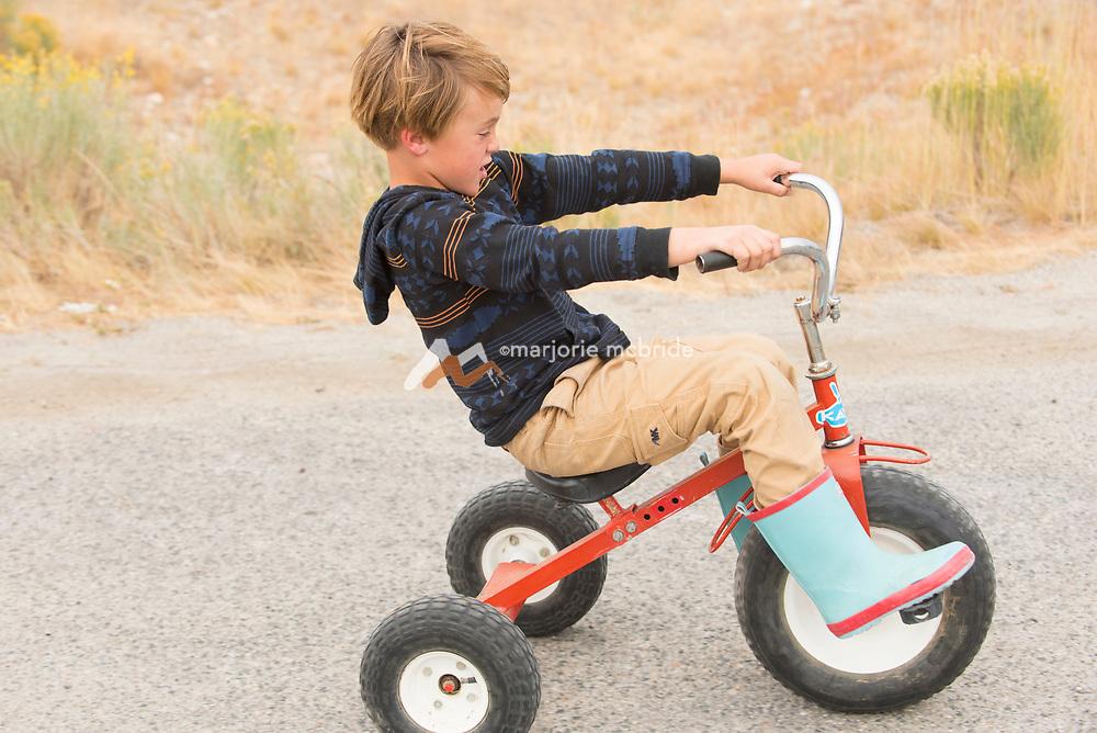 Little boy playing on trike in Stanley, Idaho. MR