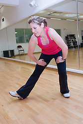 Woman stretching her legs in an aerobics class at her sports leisure centre,