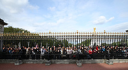 People gather outside Buckingham Palace to take pictures on their mobile phones of the notice placed on an easel in the palace's forecourt in London to formally announce the birth of a baby boy to the Duke and Duchess of Sussex.