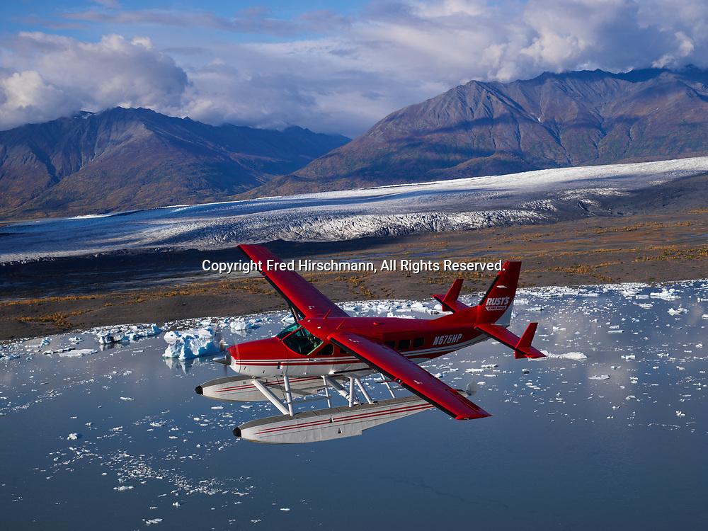 Rust's Flying Service Cessna 208 Caravan on floats flying above Lake George with Knik Glacier beyond, Alaska.