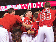 The Angels' Johnny Giavotella is mobbed by teammates after his game-winning double in the bottom of the ninth inning to give the Halos a 4-3 victory over the Seattle Mariners Wednesday night at Angel Stadium.