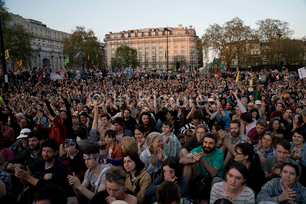 The audience at the audience at the Marble Arch Extinction Rebellion camp cheer Greta Thurnberg. Several roads were blocked across four sites in central London, by the Extinction Rebellion climate change protests, April 2019.