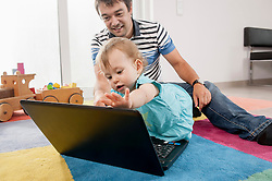 Baby father playing carpet laptop computer