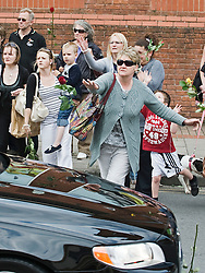 © licensed to London News Pictures. 18/04/2011. Swindon, UK. People throw flowers on to the funeral cortege carrying the coffin of murder victim SIan O'Callaghan passes on its way to a private service in Swindson, Wilts today (18/04/2011). The body of the 22 year-old PA was found in wooded area in Uffington, Oxfordshire following her disappearance while on a night out in Swindon.  Please see special instructions for usage rates. Photo credit should read Ben Cawthra/LNP