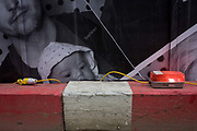 A baby's face on a construction site hoarding peers over the top of a timber traffic barrier and wiring, on the corner of Limeburner Lane and Ludgate Hill, EC4. Yellow wiring and an illuminated red light alerts others to the industrial hazard. The construction and development company Skanska is responsible for its design, maintaining a clean and tidy site, separating the dangers of the site and Londoners at street level.