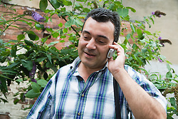 Bulgarian man outside in garden using a mobile phone,