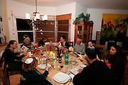 Jewush family around the Traditional sedder table set for a Jewish Festive meal on Passover (transliterated as Pesach or Pesah), also called chag HaMatzot - Festival of Matzot is a Jewish holiday beginning on the 15th day of Nisan, which falls in the early spring and commemorates the Exodus and freedom of the Israelites from ancient Egypt. Passover marks the birth of the Jewish nation, as the Jews were freed from being slaves of Pharaoh and allowed to become servants of God instead.