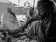 A Holy man (Sadhu) prepares hashish in his tent at the Kumbh Mela festival in Prayagraj, India.