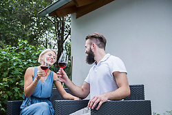 Young couple enjoying red wine in garden, Bavaria, Germany