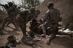 Afghan and US soldiers and officers from 1-75 CAV 101st Airborne Division tend to the life-threatening injuries of a US soldier after he was wounded when a remote-controlled IED was detonated as a group of US and Afghan soldiers were entering the Kandahari village of Zenadan in the province's Zhari District on Sept. 17, 2010. The IED - which appears to have been detonated in a deliberate attempt to kill an US and Afghan lieutenant colonel who were in the column - also killed an Afghan soldier
