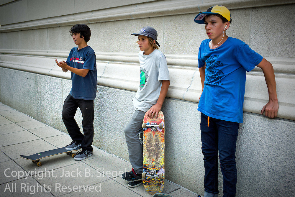 Three boys skateboarding on the south terrace of the Art Institute of Chicago on a hot summer day