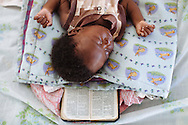A 2-month-old with gastroenteritis sleeps atop a Bible in the pediatric ward at Choscal Hospital in Cite Soleil, Port-au-Prince, Haiti. The nongovernmental organization Medecins Sans Frontieres staffs physicians and nurses at the hospital.