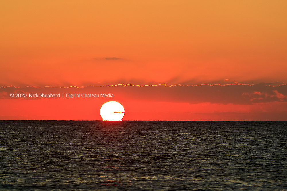 The sun sets over the calm Caribbean Sea, touching the horizon, creating a deep orange cloudscape and reflection on the waves.