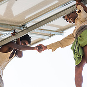 CAPTION: Workers congratulate one another after successfully completing the construction of the first solar panel at the OORJAgram Rural Enterprise Zone. LOCATION: Diara Rasulpur, Saran District, Bihar, India. INDIVIDUAL(S) PHOTOGRAPHED: From left to right - Mangal Ray and Jairam Kumar Ray.