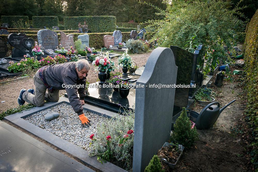Nederland,  Den Bosch, Dick Gilsing maakt het graf schoon van zijn schoonouders op kerkhof Orthen