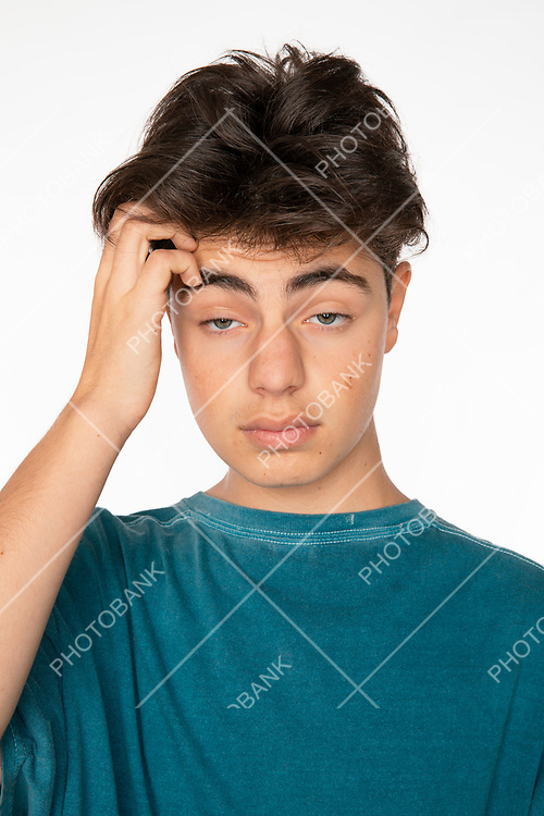 Close up portrait of a young boy scratching his head with his right hand desperate from life's problems. White background