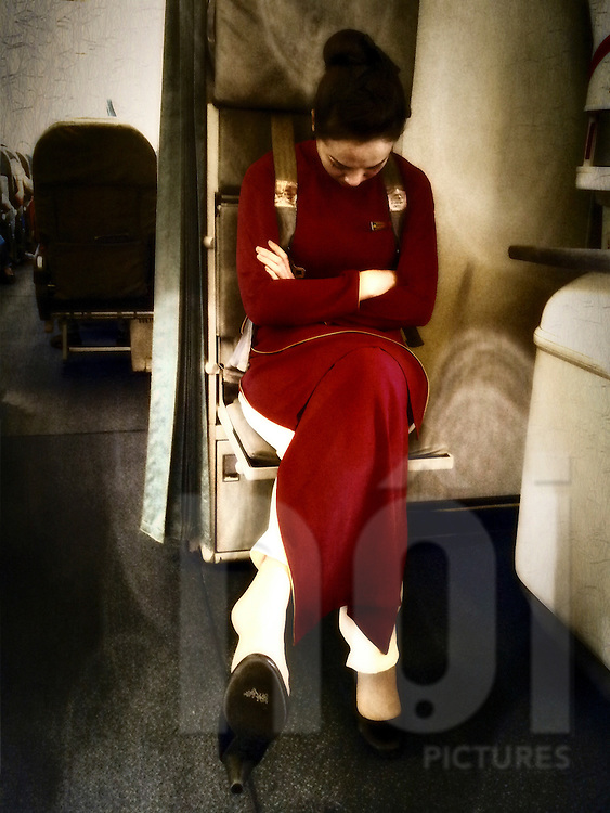 A Vietnam airlines hostess takes a nap during take off, Vietnam, Southeast Asia