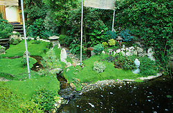 Oriental style garden with water, rocks and bamboo screen