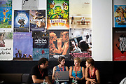 Participants at the Sarajevo Film Festival network with each other in a room full of movie posters