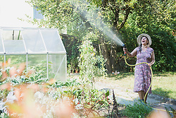 Senior woman watering plants in the garden, Altoetting, Bavaria, Germany