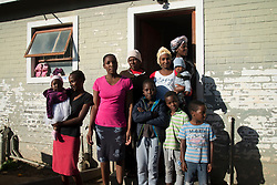 "Some of the residents of this multi-family household in Jamestown, in the Cape Winelands District, stand for a portrait on May 30, 2020. Twelve adults, six women and six men, live here with seven children. They are all from Zimbabwe and most of them have not been able work during lockdown, as their places of employment are closed. Being from another country, they also didn't qualify for assistance, explained Lenia Tafirey, (top right) who spoke for the group. However, the car-wash employer of two of the men, and a volunteer soup kitchen, made sure the residents have had food to eat since the lockdown started at the end of March. <br /> ""We all come from the same country, Zimbabwe,"" said Tafirey. ""No one is working. We are working at restaurants, and the restaurants are closed. We have no money. No work, no pay. And we are foreigners. We are not from here."" <br /> To those who ask why they haven't returned to their home country, she says: ""But the borders are closed."" <br /> Evernice Magara (2nd from top left) adds: ""It's difficult to go back, and we have no accommodation in Zimbabwe. We don't have money. We don't have nothing. We can't just go back because of Corona virus,"" she says. ""We have been getting soup every day."" PHOTO: EVA-LOTTA JANSSON"