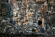 """Built around 1190 AD by King Jayavarman VII, the Bayon is a Buddhist temple incorporating elements of Hindu cosmology. The Bayon Temple is believed to represent the intersection of heaven and earth, at the exact centre of Angkor Thom.<br /> <br /> It is known for its huge stone faces of the bodhisattva Avalokiteshvara, with one facing outward and keeping watch at each compass point. The curious smiling image, thought by many to be a portrait of Jayavarman VII himself, has been dubbed by some the """"Mona Lisa of Southeast Asia."""" There are 51 smaller towers surrounding the Bayon, each with four faces of its own."""