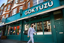 © Licensed to London News Pictures. 19/04/2020. London, UK. A man wearing a face mask walks past a Turkish restaurant in north London. <br /> It has been reported that the government scientists have a 'traffic light' plan to ease Britain out of COVID-19. According to the plan, restaurants may open during the week of 25 May but with strict seating demarcations. Photo credit: Dinendra Haria/LNP